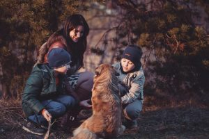 Woman, two boys and a golden retriever squatting down together in a circle
